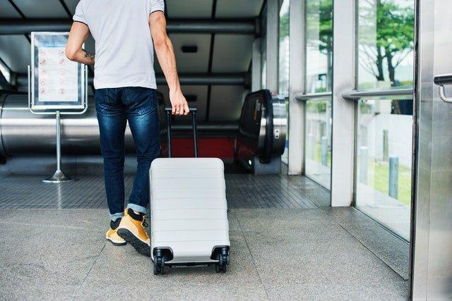 Muž na letisku ťahajúci kufor
