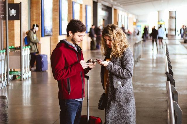 Muž a žena na letisku, ktorí pozerajú do mobilných telefónov